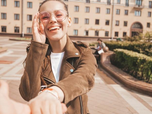 Volg mij romantisch concept jonge vrouw met lang haar buitenshuis houdt de hand van haar vriendje zich omdraaiend in zonnebril