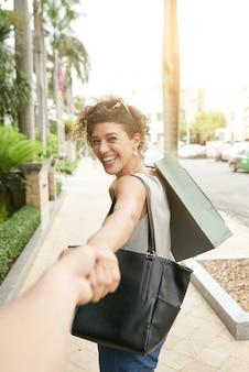 Volg mij shot van een vrouw die zich omkeert naar haar onherkenbare vrouw die haar hand vasthoudt