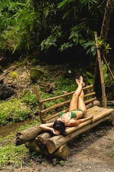 Volg mij. tevreden brunette vrouwelijke persoon die een zwempak draagt om te zonnebaden, genietend van geluiden van exotische natuur