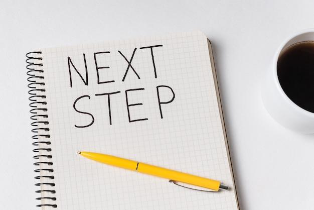 Volgende stap woorden met inscriptie handschrift in kladblok. close-up van notebook, pen en kopje koffie