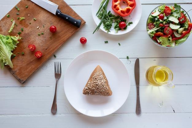 Volkoren brood op plaat en salade op een witte houten achtergrond van tomaten, komkommers, sla en rode peper. gezond eten concept.