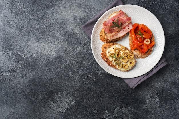 Volkoren brood sandwiches met roomkaas, spek en olijven ingeblikte paprika met tomaat op een bord.