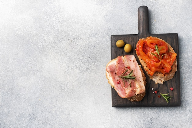 Volkoren broodsandwiches met roomkaas, bacon en ingeblikte pepers met tomaat op een houten snijplank.