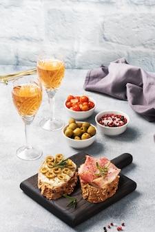Volkoren broodsandwiches met roomkaas, bacon en olijven op een houten snijplank. een glas witte wijn.