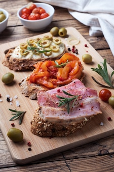 Volkoren broodsandwiches met roomkaas, spek en olijven in blik paprika met tomaat