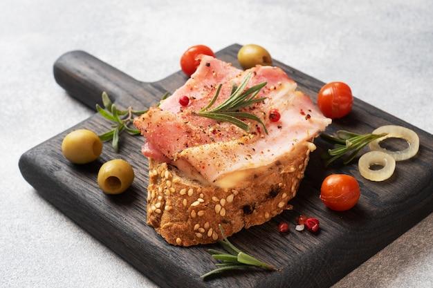 Volkoren broodsandwiches met roomkaas, spek op een houten snijplank.