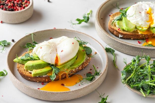 Volkoren geroosterd brood met avocado, gepocheerd ei, zachte kaas en spruitjes op wit Premium Foto
