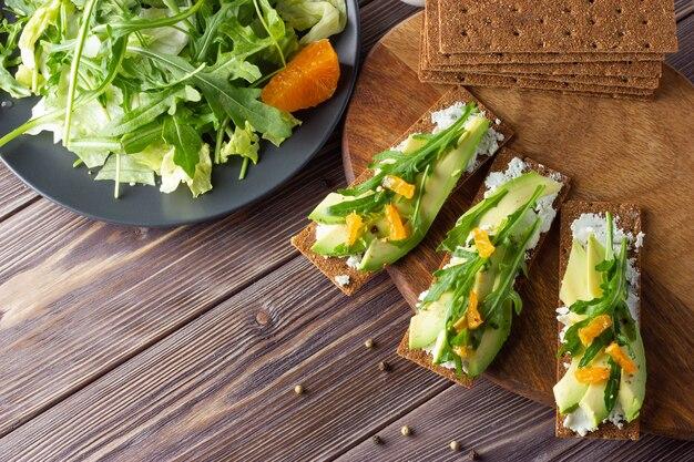 Volkoren knapperig brood met kaas, avocado en verse bladeren met salade op houten achtergrond.