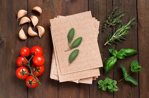Volkoren lasagnebladen, tomaten, knoflook en kruiden op houten lijst