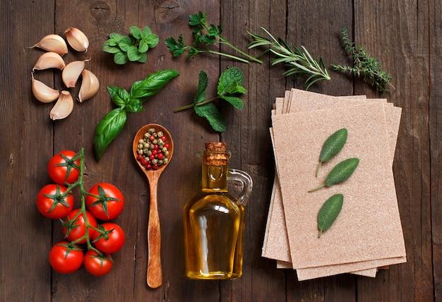 Volkoren lasagnebladen, tomaten, knoflook, olijfolie en kruiden op houten tafel