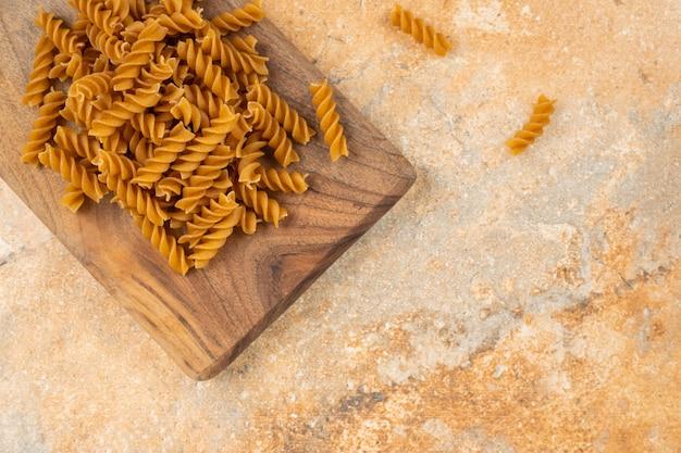 Volkoren pasta fusilli op een bord, op het marmer.