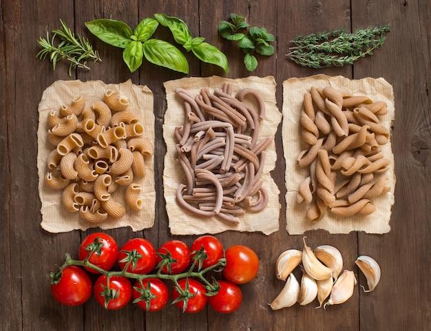 Volkoren pasta, groenten, kruiden en olijfolie op houten tafelblad weergave