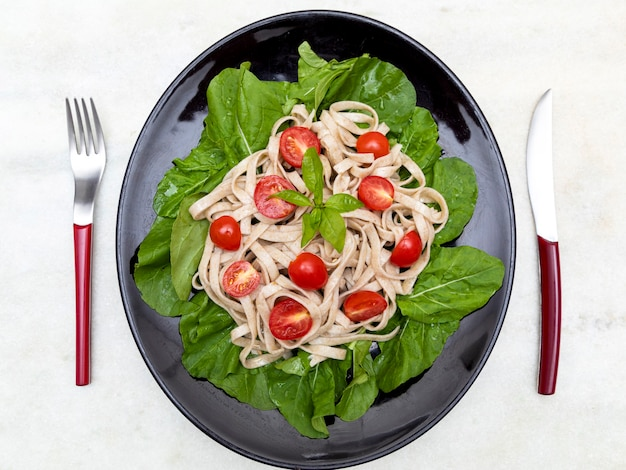 Volkoren pasta met groene bladeren van rucola en kersentomaat op zwarte plaat en witte marmeren achtergrond