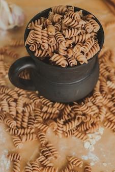 Volkoren pasta van organische gespeld vallen uit een zwarte mok