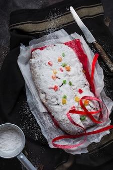 Volkoren stollen met rozijnen en poedersuiker op een linnen servet met een zeef, rood lint over de oude donkere betonnen achtergrond. traditionele duitse kersttaart. bovenaanzicht.