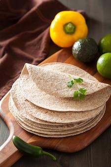 Volkoren tortilla's op een houten bord en groenten