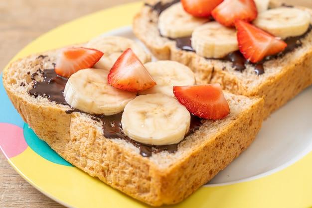 Volkorenbrood geroosterd met verse banaan, aardbei en chocolade als ontbijt Premium Foto