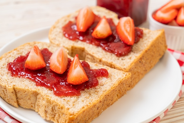 Volkorenbrood met aardbeienjam en verse aardbeien