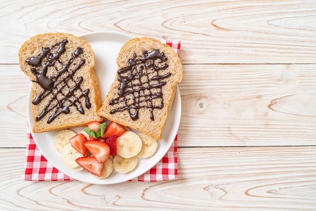 Volkorenbrood met verse banaan, aardbei en chocolade