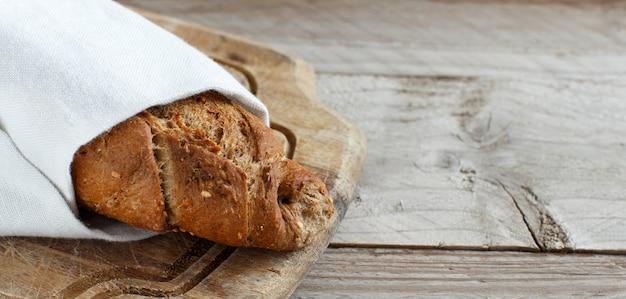Volkorenbrood op een houten tafelblad bekijken