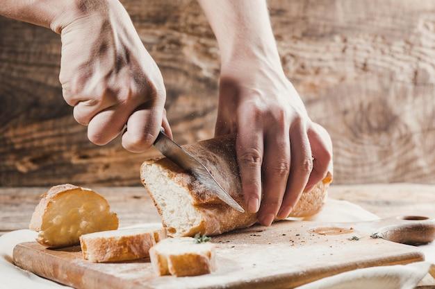 Volkorenbrood op keuken houten plaat gezet met een chef-kok die gouden mes houdt om te snijden.