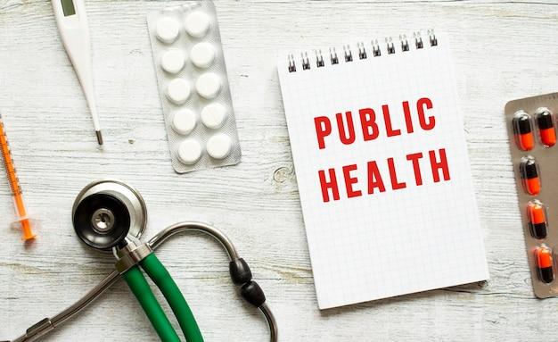 Volksgezondheid is geschreven in een notitieboekje op een witte tafel naast een stethoscoop