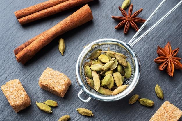 Volle kardemomkorrels, een kaneelsteranijs en rietsuiker. detailopname. ingrediënten voor het maken van de indiase drink masala thee.