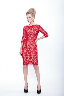 Volle lengte afbeelding van een jonge vrouw in rode jurk en accessoire, op witte achtergrond. verticale weergave.