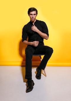Volle lengte afbeelding van een vrolijke knappe sterke jonge man in zwarte kleding, zittend op een stoel op gele achtergrond.