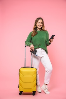 Volle lengte blije blonde vrouw in groene trui die zich voorbereidt om te trippen terwijl ze een smartphone vasthoudt en naar de voorkant kijkt over de roze muur