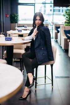 Volle lengte foto van aantrekkelijke jonge dame in zwarte jas zittend in een cafetaria terwijl het drinken van koffie.