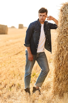 Volle lengte foto van aantrekkelijke man 30s wandelen door gouden veld, en staande in de buurt van grote hooiberg tijdens zonnige dag