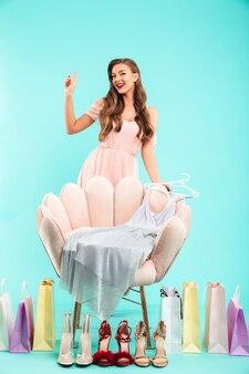 Volle lengte foto van blanke mooie vrouw 20s in kleding winkelen terwijl poseren met veel kleurrijke tassen en kleding, geïsoleerd over blauwe muur