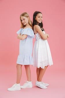 Volle lengte foto van brunette en blonde meisjes die jurken dragen die glimlachen en kijken terwijl ze rug aan rug staan met gevouwen armen.
