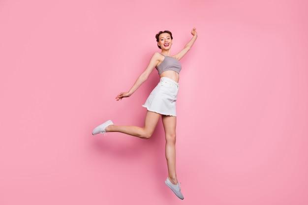 Volle lengte foto van charmant schattig meisje sprong greep hand willen vangen vliegende parasol dragen casual stijl kleding sneakers geïsoleerd over roze kleur