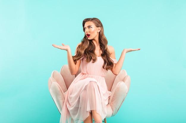 Volle lengte foto van charmante vrouw in jurk zittend in fauteuil met handen overgeven terwijl opzij kijken op copyspace, geïsoleerd over blauwe muur
