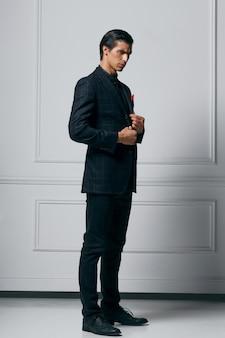 Volle lengte foto van een stijlvolle zelfverzekerde jonge man in zwart pak op zoek in profiel, op een witte achtergrond.