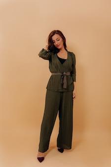 Volle lengte foto van elegante stijlvolle vrouw stijlvolle broekpak dragen tegen beige muur