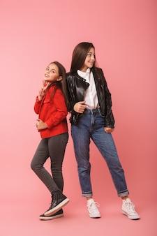 Volle lengte foto van europese meisjes in casual staande samen, geïsoleerd over rode muur
