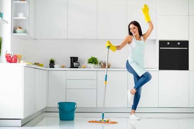 Volle lengte foto van gekke vrolijke gilr wasvloer in de keuken met dweil wil ontspannen plezier stel je voor dat ze danst clubbing handen opsteken schreeuwend binnenshuis met gestippelde schort