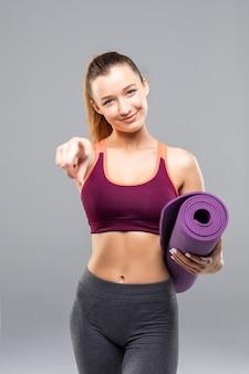 Volle lengte foto van gelukkige fitness vrouw met fitness mat en wijst naar jou
