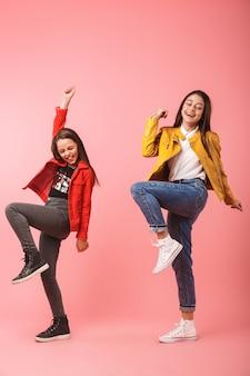 Volle lengte foto van gelukkige meisjes in casual dansen samen, geïsoleerd over rode muur