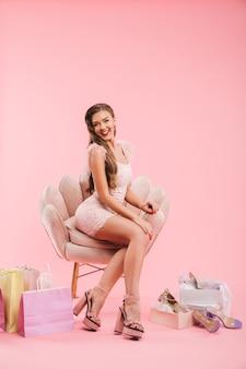Volle lengte foto van gelukkige vrouw in jurk kijken zittend in fauteuil met boodschappentassen en schoenen, geïsoleerd over roze muur