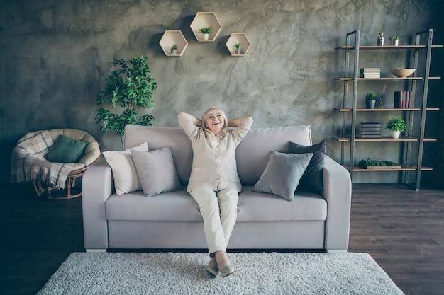 Volle lengte foto van geweldige blonde oude oma goed humeur handen achter het hoofd kijken plafond genieten van nieuwe huisstijl ontwerp zitten comfort sofa divan woonkamer binnenshuis