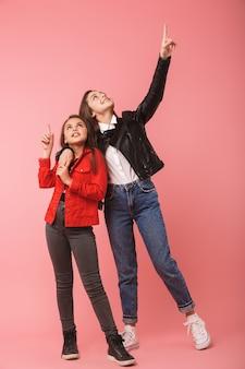 Volle lengte foto van glimlachende meisjes in casual staande samen, geïsoleerd over rode muur