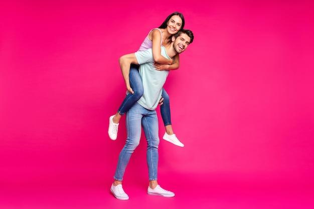 Volle lengte foto van grappige kerel en dame die meeliften houden van de beste vrije tijd dragen vrijetijdskleding geïsoleerde levendige levendige roze kleur achtergrond