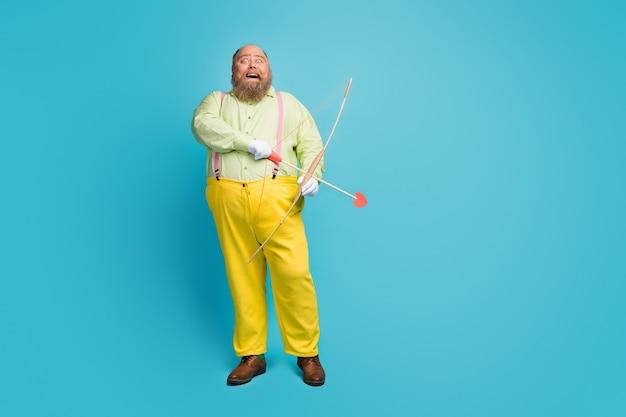 Volle lengte foto van grappige man met overgewicht pijlen schieten