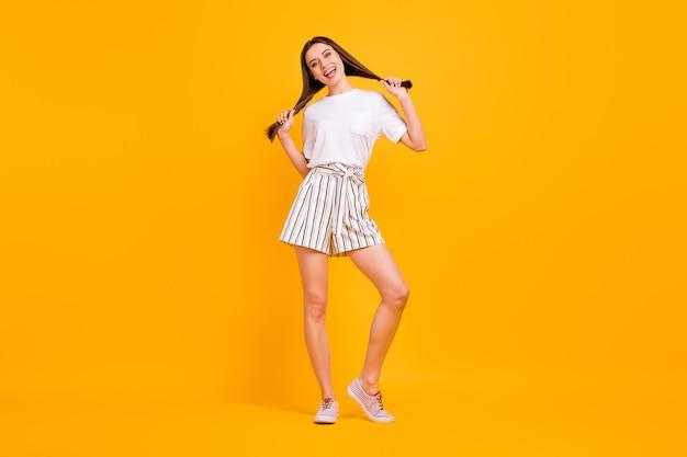 Volle lengte foto van grappige speelse dame genieten van zonnige dag lang kapsel handen vasthouden vlechten dragen casual wit t-shirt gestreepte korte broek schoenen geïsoleerd levendige gele kleur muur