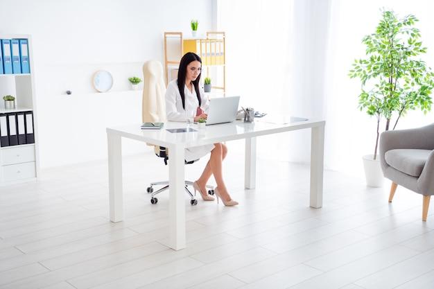 Volle lengte foto van het mooie doc lady werk op laptop in het witte kantoor van het kliniekcentrum