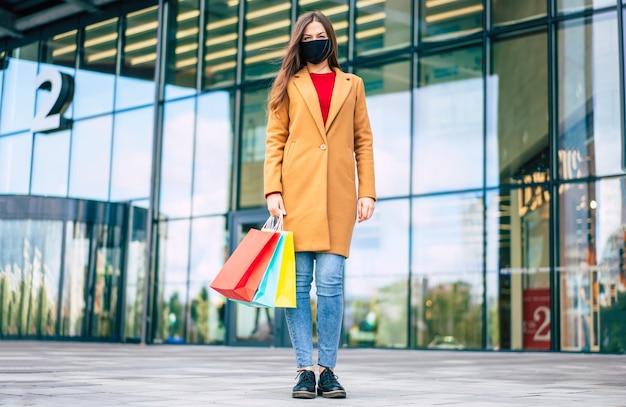 Volle lengte foto van jonge zelfverzekerde vrouw in jas en medische veiligheidsmasker met boodschappentassen is poseren op de achtergrond van het winkelcentrum